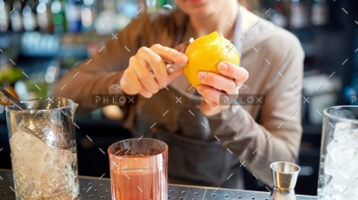 demo-attachment-18-bartender-peels-orange-peel-for-cocktail-at-bar-P97775Y