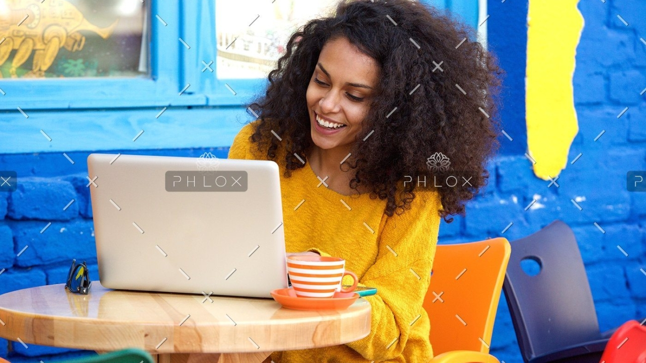 demo-attachment-29-happy-young-woman-sitting-at-outdoor-cafe-using-PFFBJ93